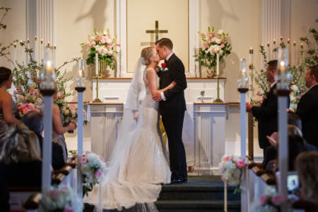 A picture of a bride and groom standing at the altar of the Gloria Dei Lutheran Church where they are in the center and the bride is wearing a white lace sparkly gown with a long veil and the groom is in a black tuxedo with a bright red rose on his lapel and the are holding each other and kissing with a cream wall with white wooden and white and pink flower arrangements in the background with white wooden pews that are holding tall lit candles which are in the side foreground and out of focus.
