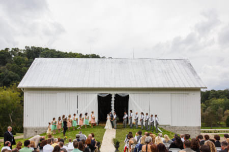A bird's eye view of a bride and groom with their mint and peach colored wedding party standing on a grassy hill in front of the opening of a white barn draped in white tulle at the Christmas tree farm called Running River Farm located outside the Mohican State Park in Loudonville, Ohio.