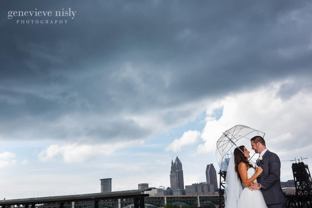 Eric and Patricia stand under an umbrella with the Cleveland skyline in the background during their Marriott Key Center wedding.