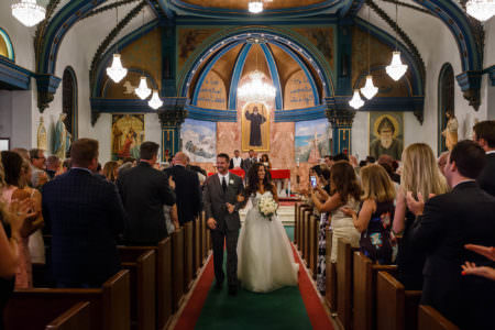 A bride and groom walk back down the center red and green carpeted aisle arm and arm smiling at the wedding guests standing on either side form wooden pews in the brightly painted sanctuary of St. Maron Church where the back wall is white with blue arched beams and the back wall painted in golds and greens with scenery and saints painted on it.