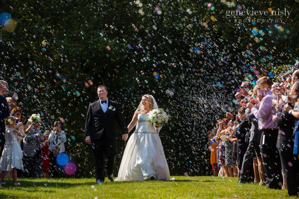 Ken and Lauren walk through bubbles during their post-ceremony bubble exit celebration at Stan Hywet Hall and Gardens in Akron, Ohio.