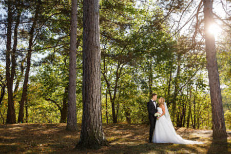 An outdoor picture a bride in her strapless white gown and her long veil trailing behind her holding her white bouquet while she stands toe to toe with her groom in a black tuxedo with a white shirt and black bow tie smiling at each other in the left side of the photo in the middle of very tall pine trees at the Horseshoe Lake Park with the sun peeking around the trunk of a tree in the upper right corner.