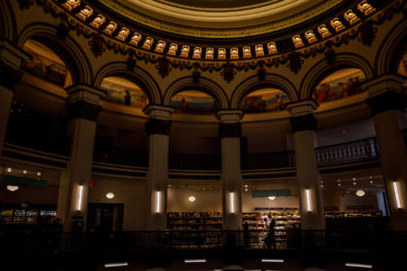 An image of a bride and groom embracing at a distance in the darkened Heinen's with a light shining on them set inside the historic Cleveland Trust Rotunda building in downtown Cleveland.