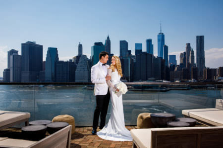 A bride in her gown and a grown in a white and black tux look into each other's eyes standing on the rooftop bar of 1 Hotel Brooklyn Bridge overlooking the lower Manhattan skyline.