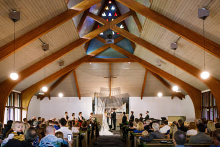 An image of a bride and groom facing each other and holding hands at the altar of Chesterland Community Church with the wedding party standing up with them and a large metal pipe organ on the back wall with a wooden cross in front and a high wooden beamed ceiling.
