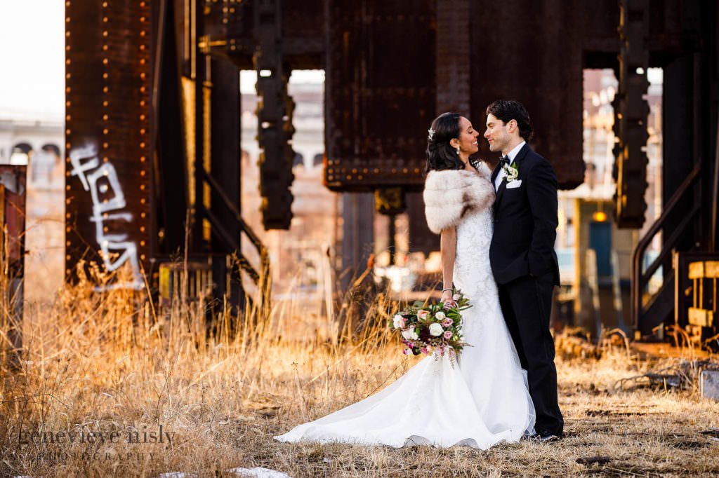 Tim and Monique embrace in front of an old bridge structure in Downtown Cleveland during their Cleveland Union Club wedding.