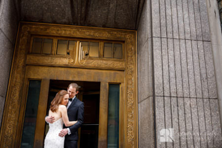 Max and Emily in front of a historic gold door in downtown Cleveland during their winter wedding at the Cleveland Museum of Art.