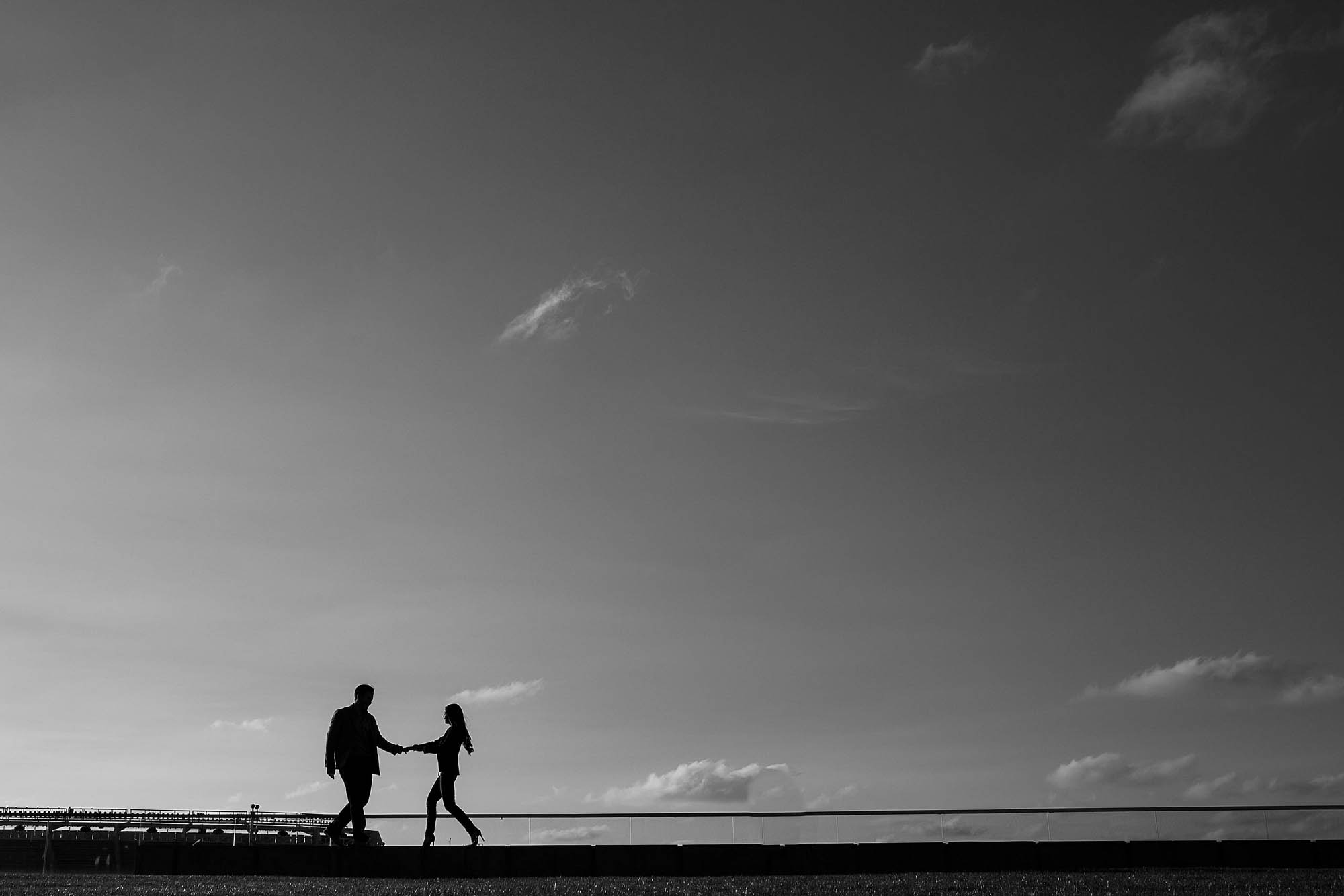 Black and white silhouette of a couple walking hand in hand against the sky in Cleveland.