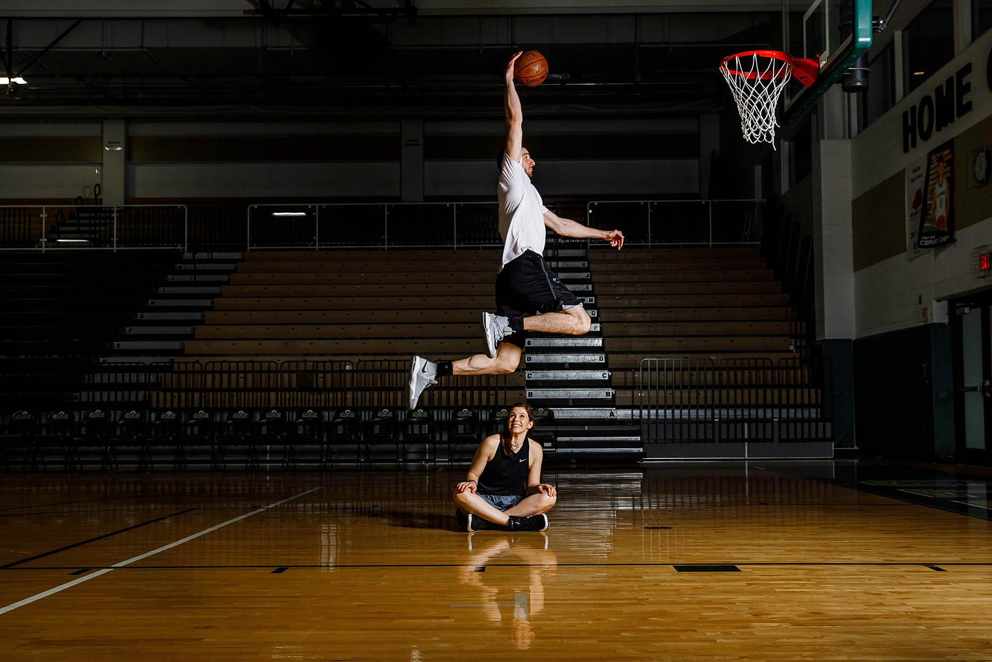NBA player Kosta Kofus jumps over his fiancée Eline to dunk a basketball.