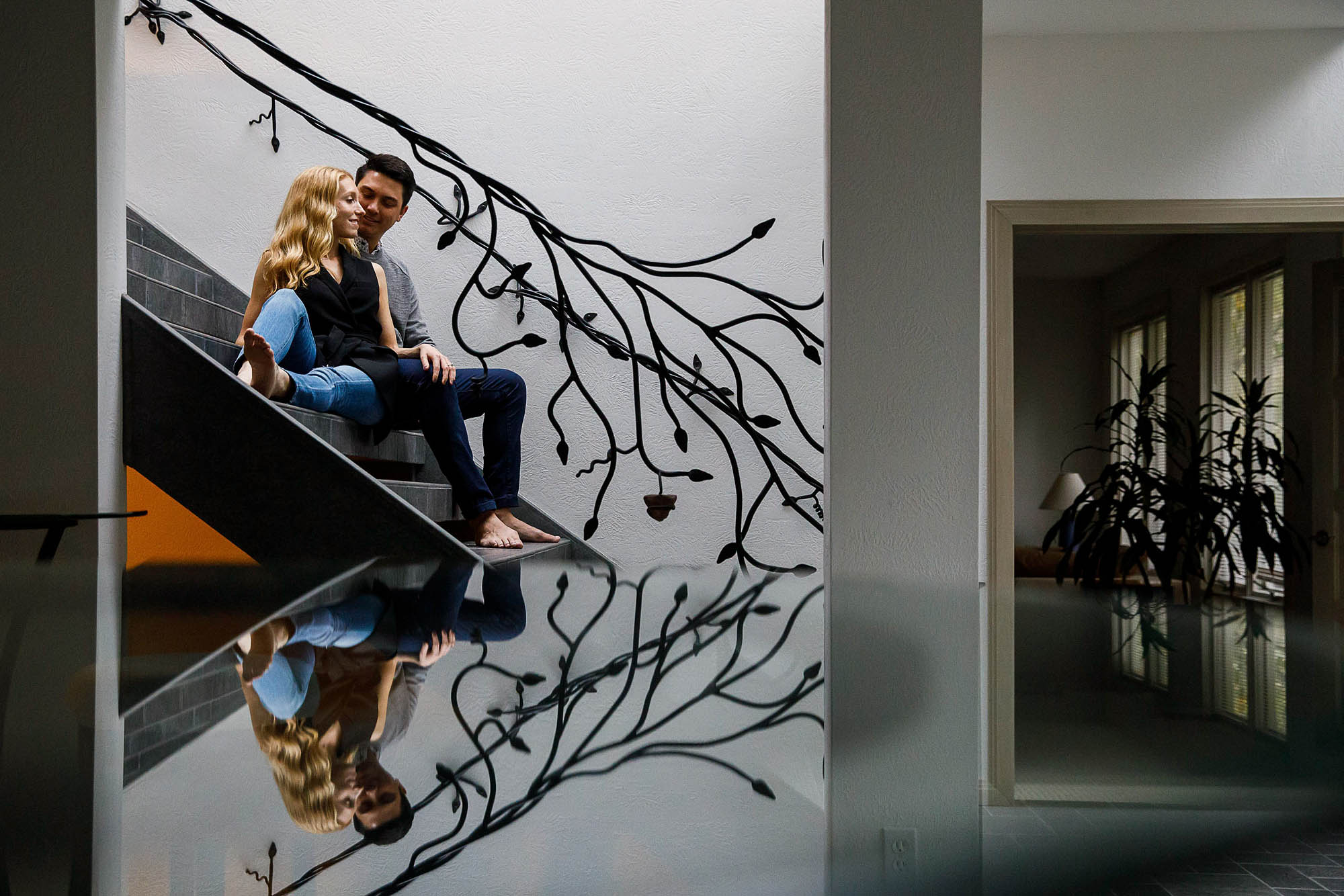 Couple seated next to each other on a staircase during their engagement photo session.