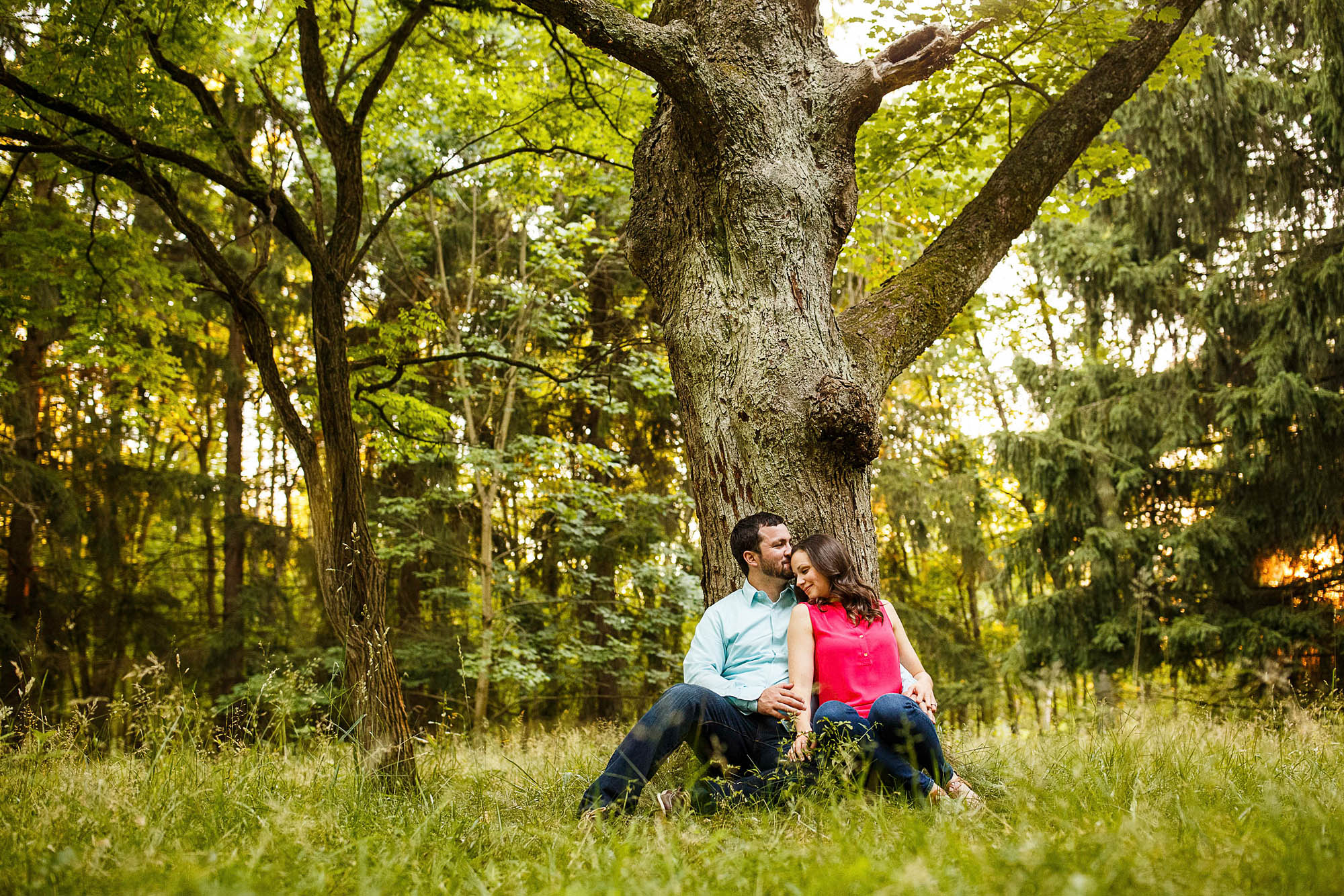 Couple snuggles under a large tree during their engagement photo session in Cuyahoga Valley National Park.