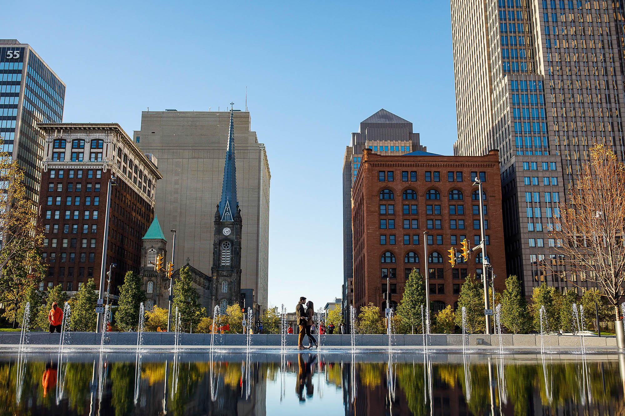 A picture of an engaged couple taken from a distance where the couple is standing in each other's arms silhouetted against the Cleveland skyline inside public square where their reflection is in the bottom of the photo.