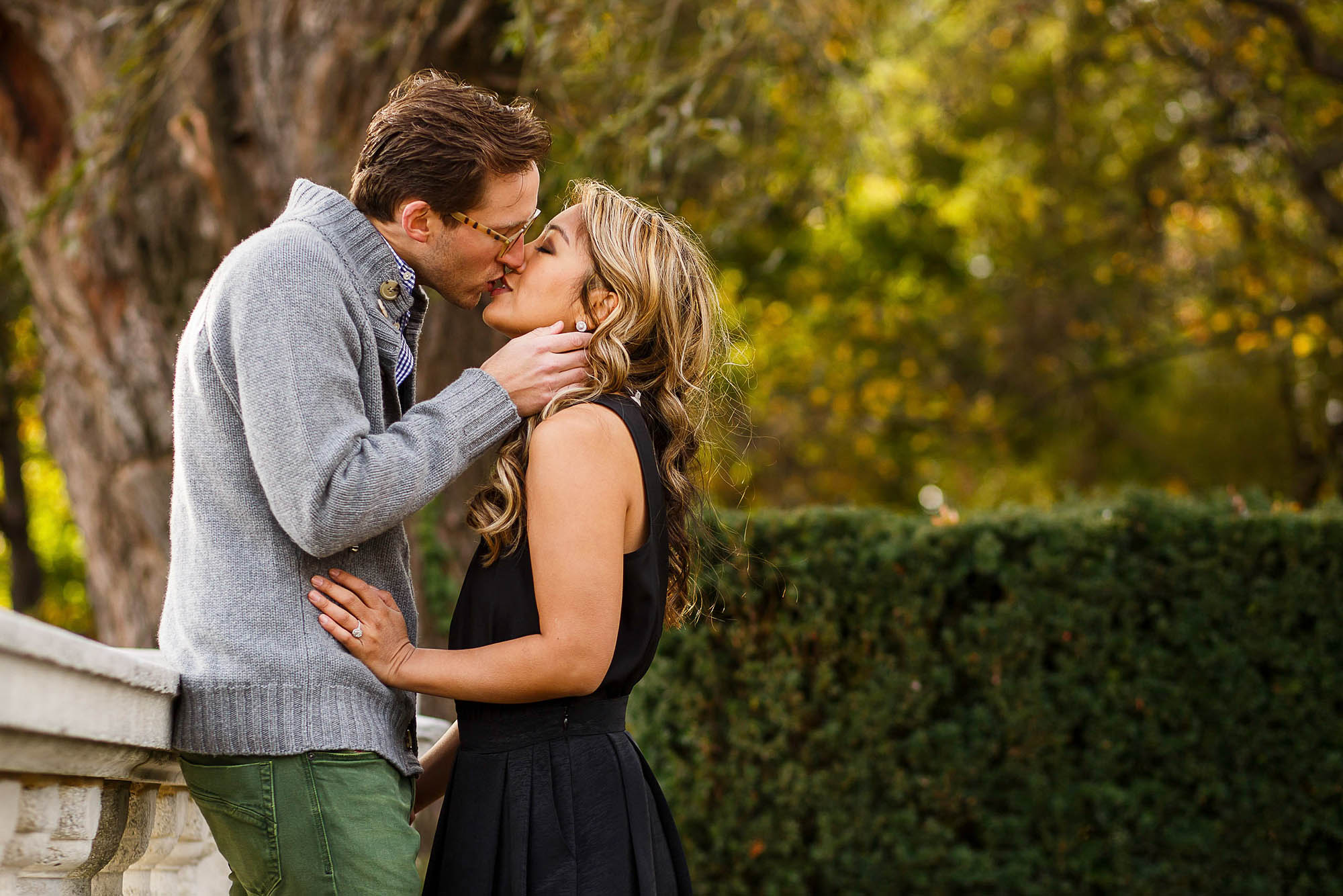 An engaged couple stand in the left side of the photo leaning in kissing in front of a dark green hedge with greenish yellow leaves out of focus in the background of the photo taken at Wade Lagoon.