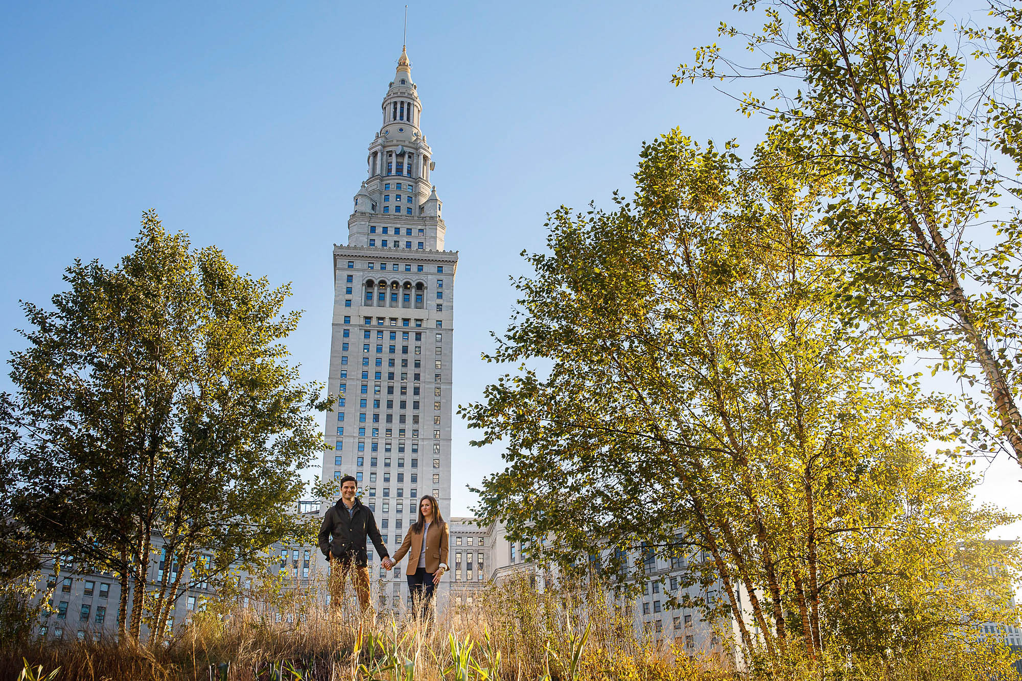 An engaged couple stands at a distance but facing the camera which is at ground level holding hands in public square of downtown Cleveland with grass out of focus in the foreground and trees to either side of the couple with a skyscraper and blue skies in the background.