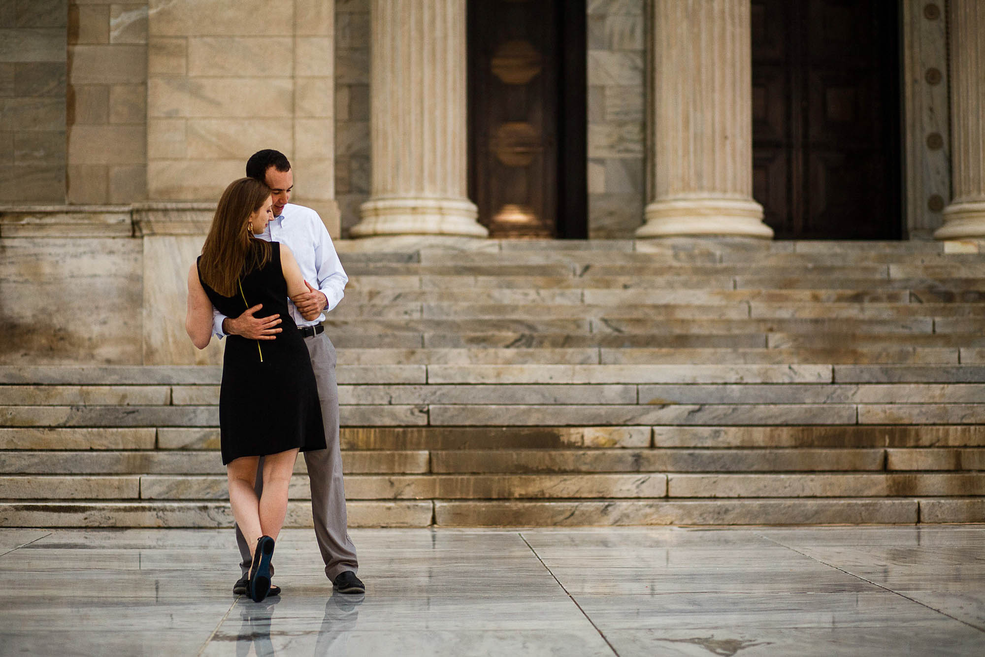 An engaged couple stand in the left of the photo holding each other with the woman's back to the camera standing outside the Cleveland Museum on a cement sidewalk with the stone steps and tall pillars of the building in the background behind them.