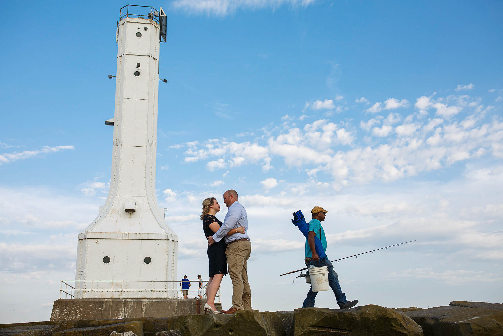 A picture of an engaged couple standing on a stone wall under a bright blue sky with puffy clouds and a crumbling white lighthouse in the background on the left and a fisherman walking out of the picture in the background on the right.