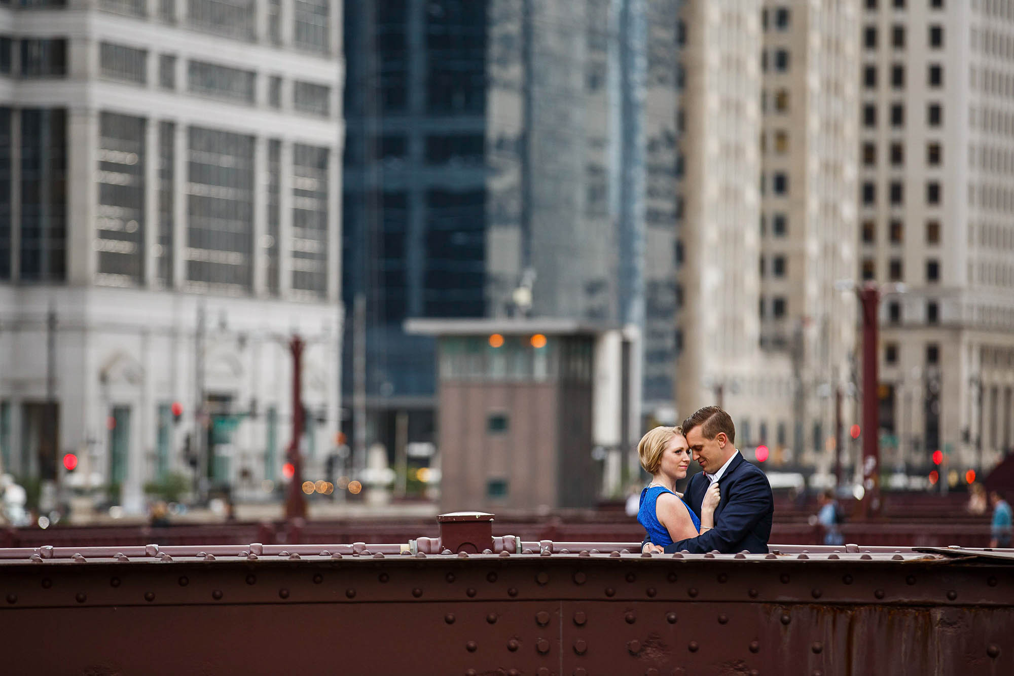 A picture of an engaged couple standing in the lower right corner of the photo behind a dark brown wall of a bridge in Chicago, IL with downtown buildings out of focus in the background behind them.
