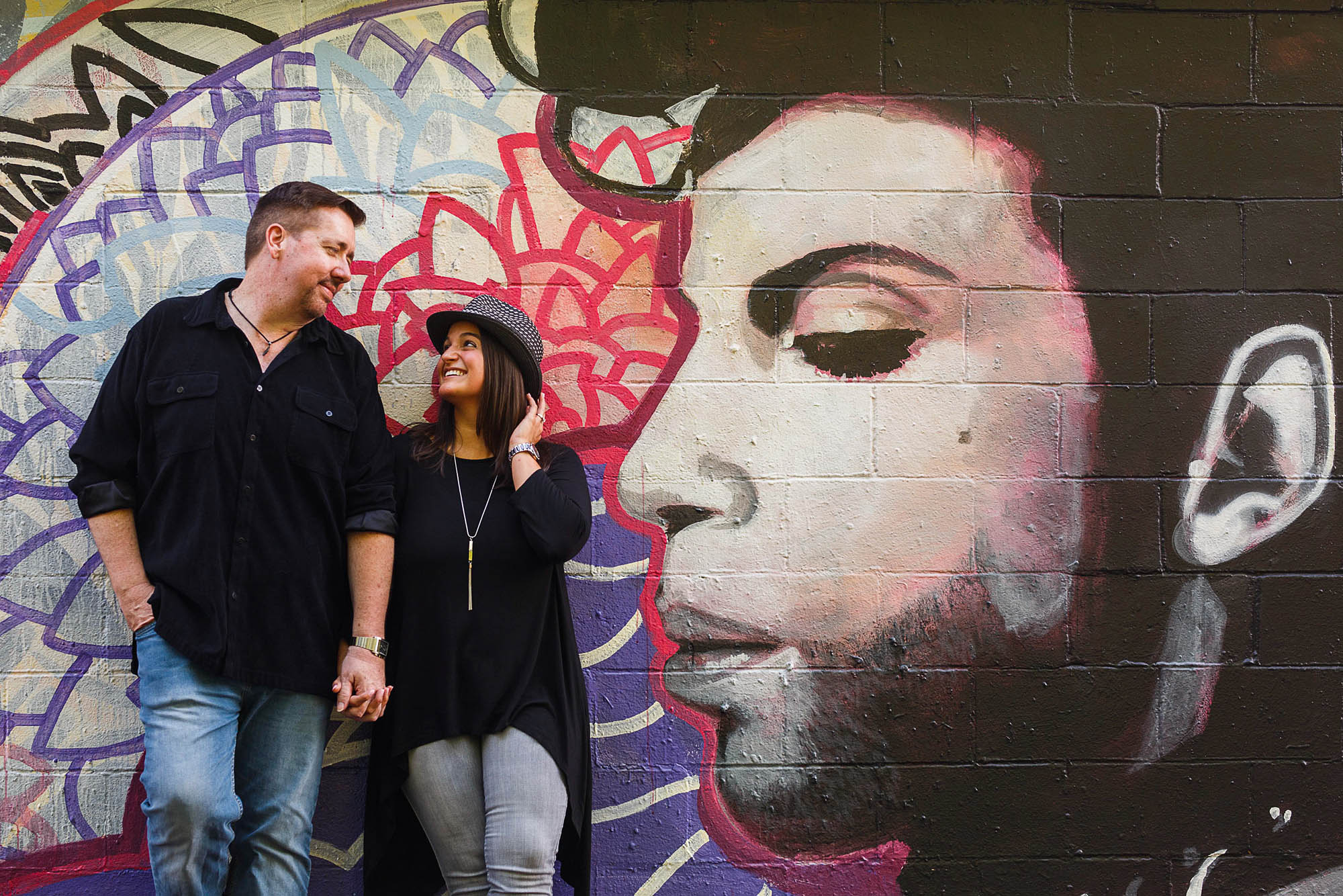 A picture of an engaged couple taken from the knees up holding hands with their heads turned toward each other while they lean back against a brick building in Dayton, Ohio that has been painted with graffiti and a large mural of Prince taking up the entire right side of the photo.