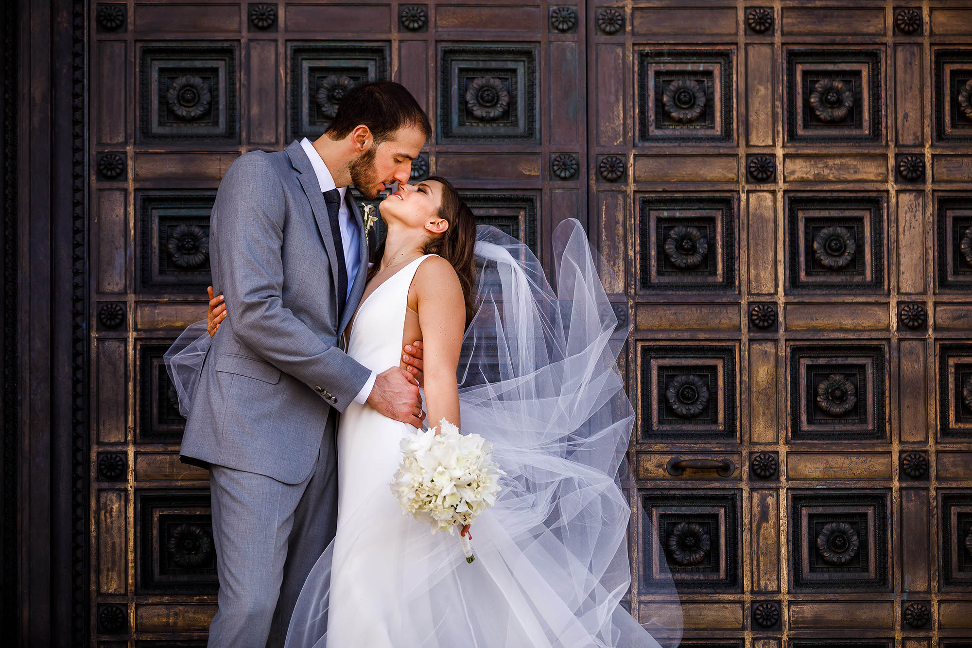We had just moments to create these bridal portraits for this bride and groom on their wedding day. We stopped by the McKinley National Memorial in Canton, Ohio on our way to the reception and posed the couple in front of the massive wooden doors. We told the groom to hold his bride tight and take a moment to enjoy this time together and we were able to create this image for them.