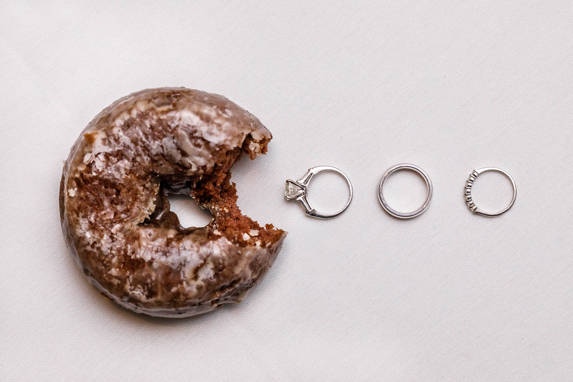 """A chocolate donut from Bakers """"eats"""" an engagement ring and wedding band set pac-man style."""