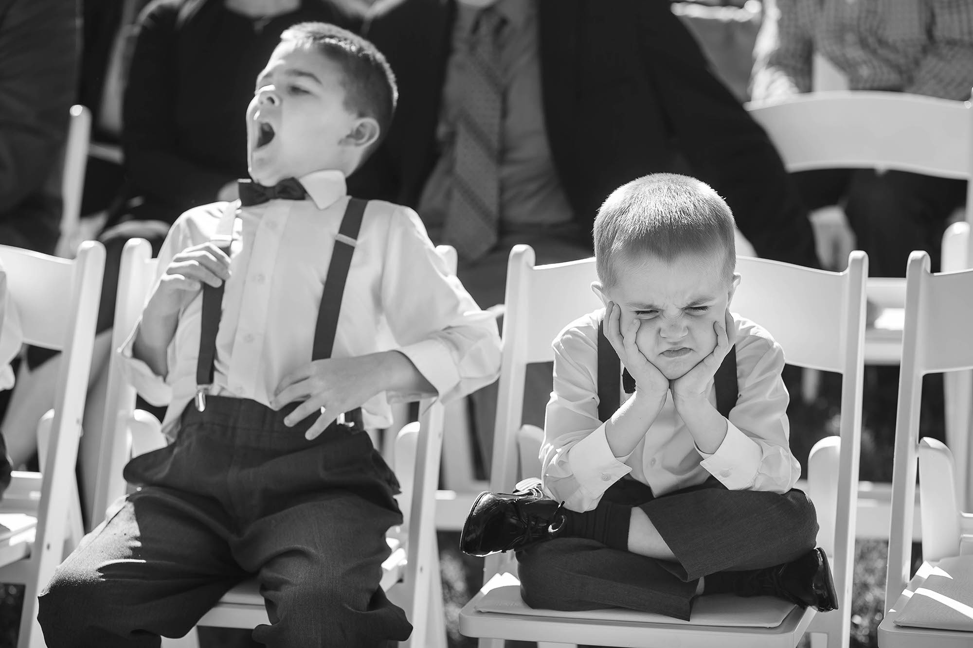 An adorable moment during an outdoor wedding ceremony held at Stan Hywet Hall and Gardens in Akron, Ohio of two little ring bearers waiting for the ceremony to finally be over.