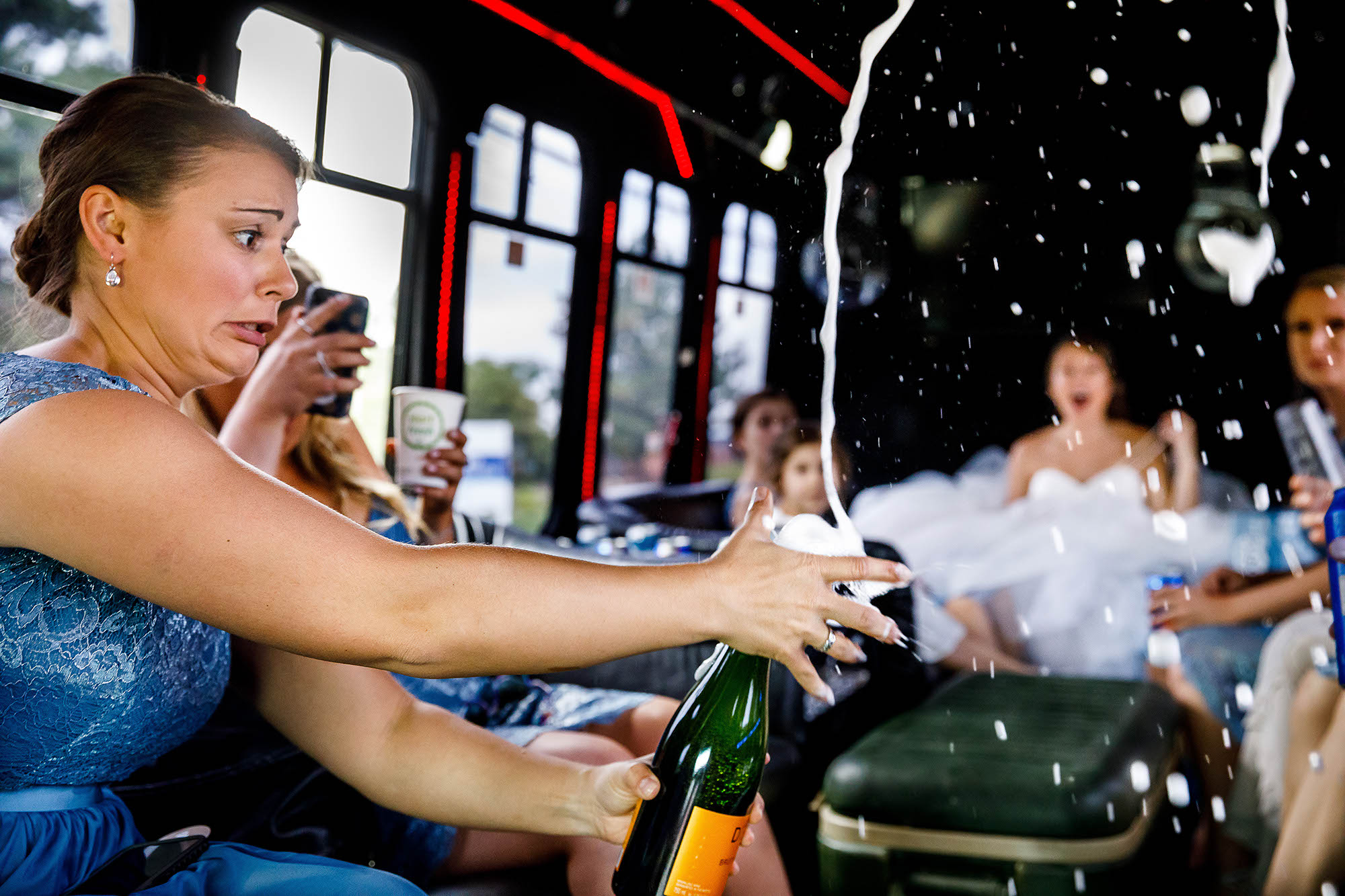 A bridesmaid grimacing while popping a champagne cork in a party bus heading to the Mapleside Farms ceremony in Cleveland, Ohio.
