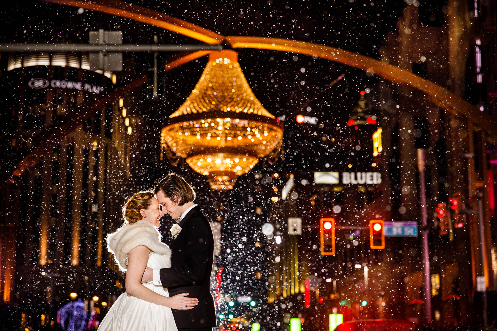A bride and groom under the chandelier at Playhouse Square as the snow gently falls behind them.