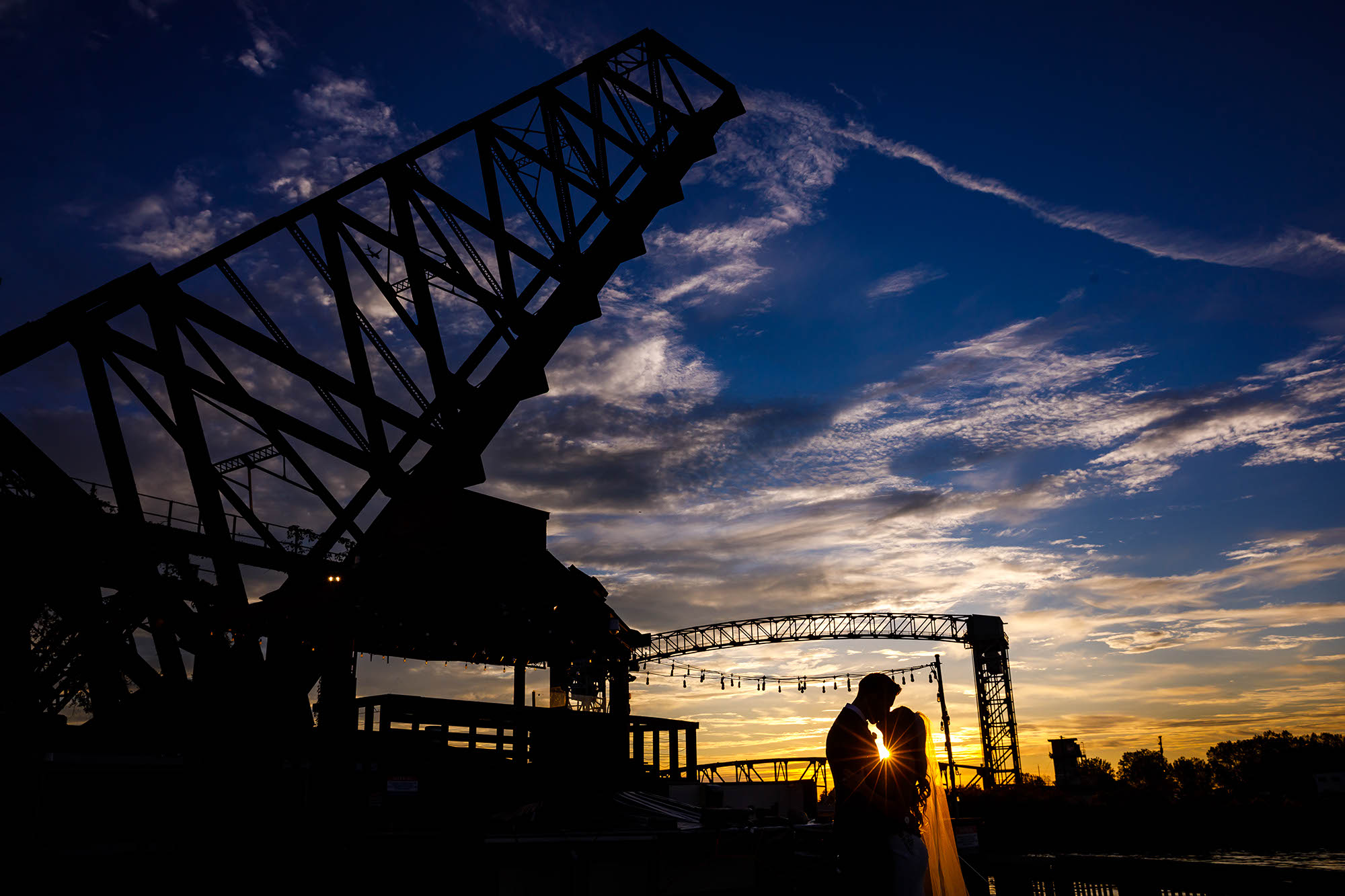 A beautiful sunset photo of a bride and groom kissing at dusk after their wedding ceremony on the West Bank of the Flats in downtown Cleveland, Ohio.