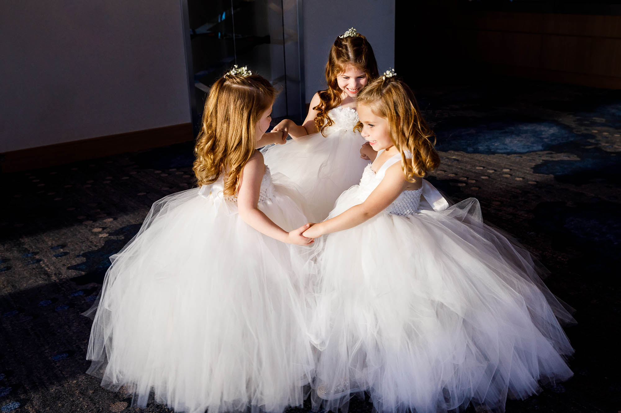 Flower girls playing and spinning in the sunlight shining through the windows at The Hilton Downtown Cleveland.