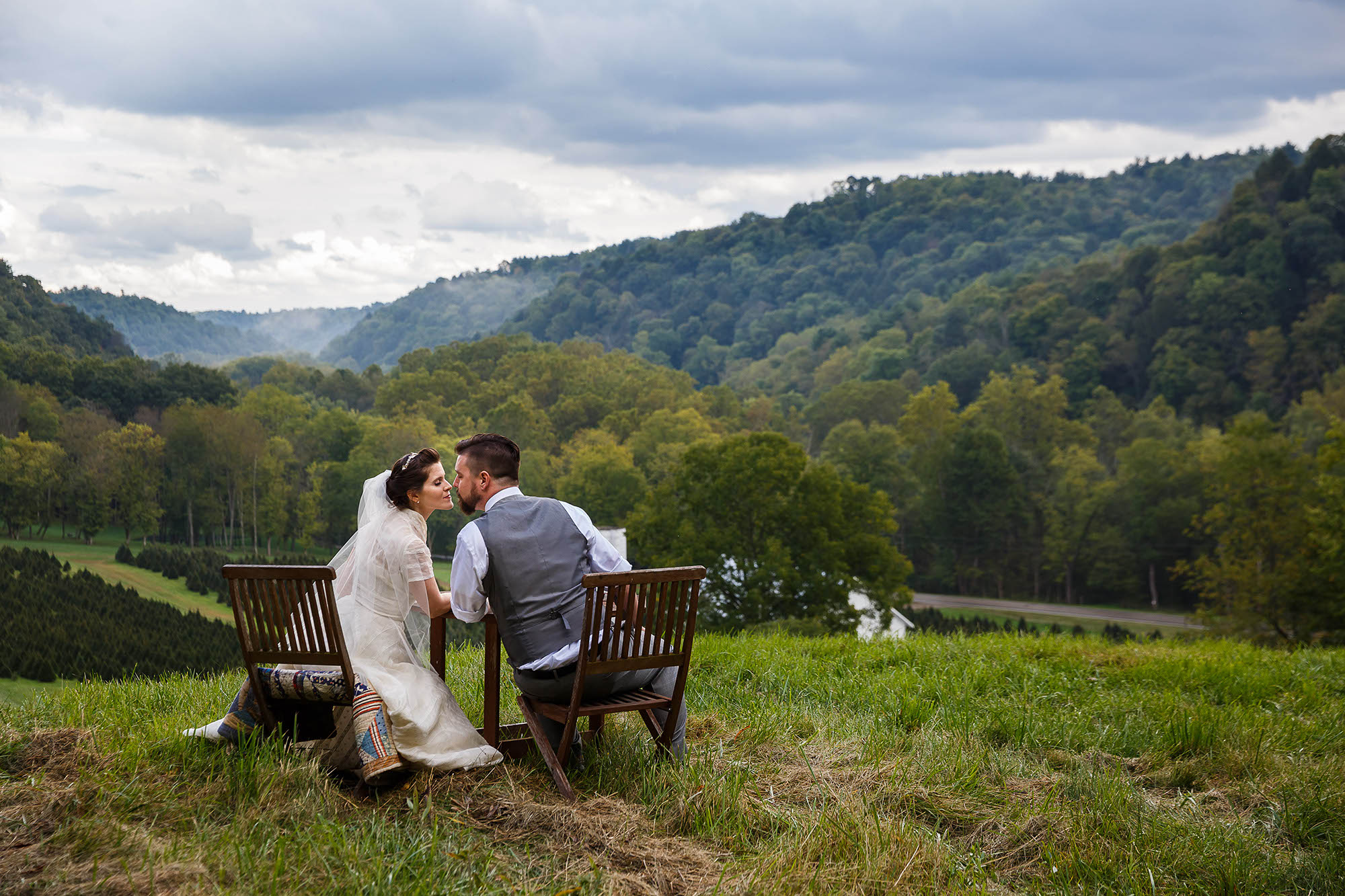 A bride and groom lean in for a kiss on a green hillside overlooking rolling hills full of lush green trees at the Running River Farm in the heart of Mohican State Park in Ohio.
