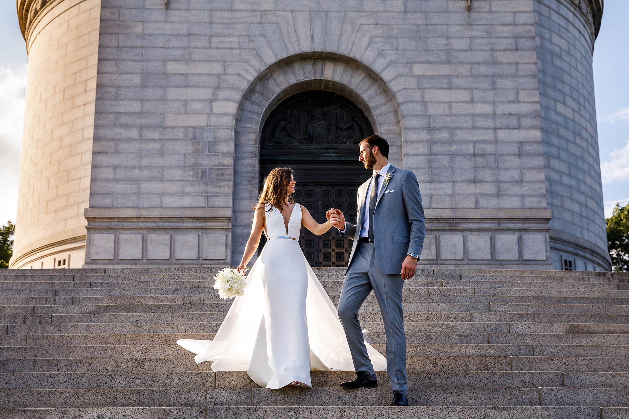 Bride and groom walk hand in hand down the steps of the McKinley Monument in Canton, Ohio on a beautiful, sunny day.
