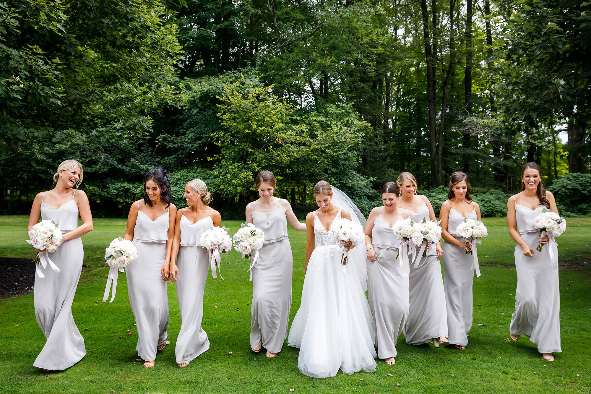A bride walking the lush green grounds of The Country Club in Hunting Valley, Ohio with her bridesmaids as they carry their bouquets before the wedding ceremony.