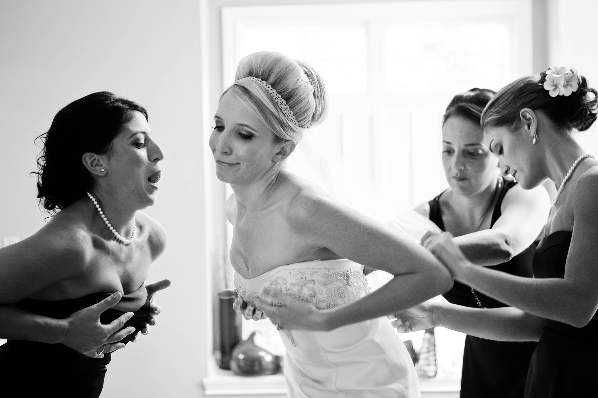 Noelle and her bridesmaids joke around as Noelle's dress is being laced up.