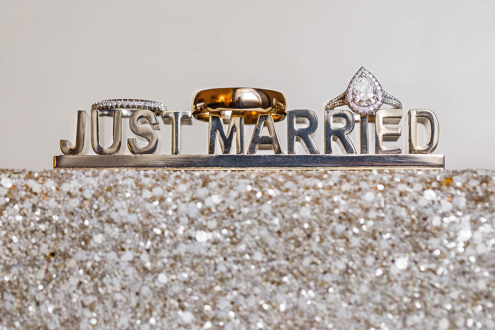 """Wedding and engagement rings on top of a sparkly """"Just Married"""" clutch at the Union Club Downtown Cleveland, Ohio."""
