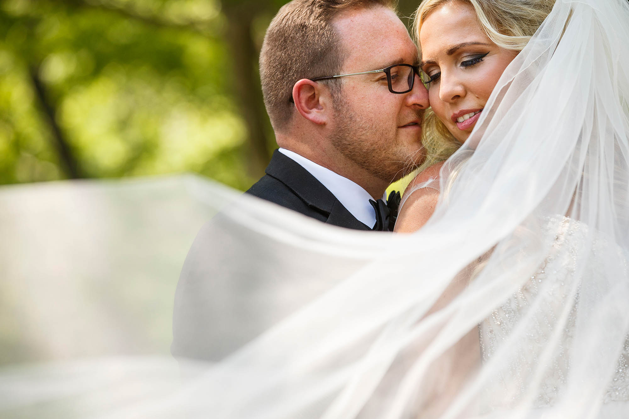 A romantic portrait of a wedding couple with the veil in the wind on the grounds of the Cultural Gardens in Cleveland, Ohio.