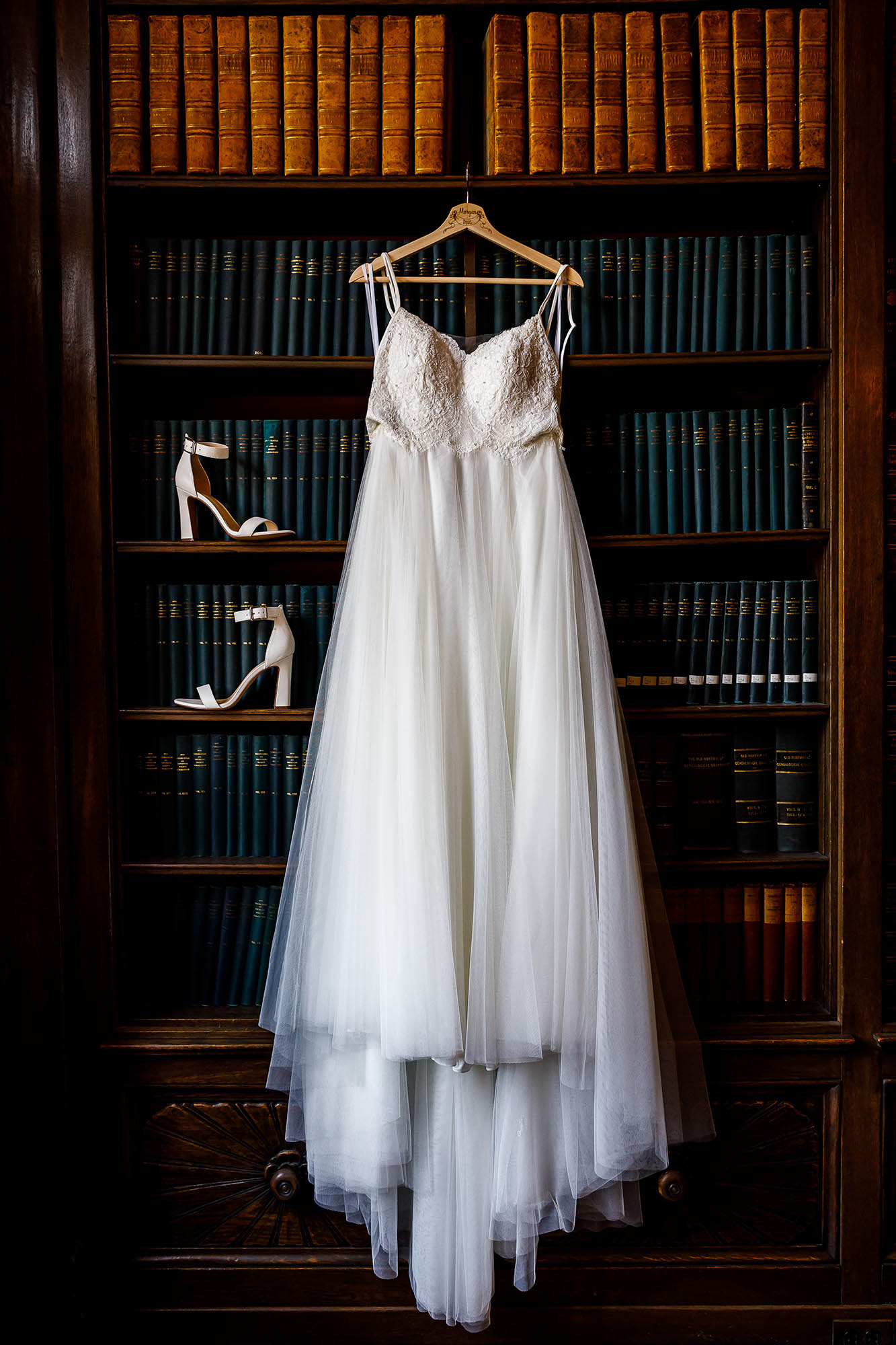 The bride's shoes stacked and her wedding gown hung from a bookshelf at the Western Reserve Historical Society in downtown Cleveland, Ohio.