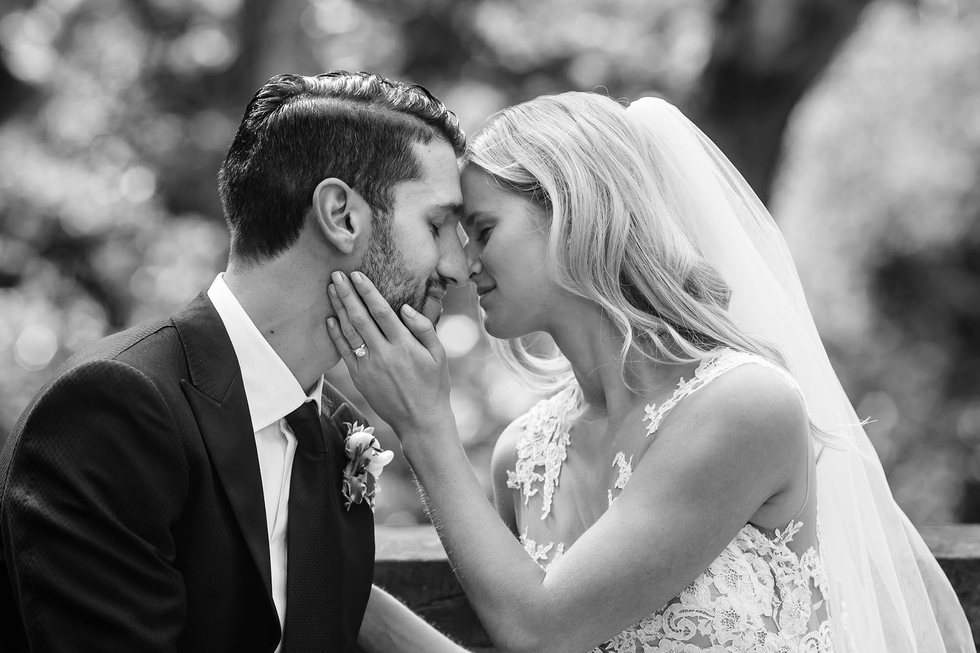 Newly married couple sits foreheads pressed together and the bride gently touching the grooms face on the grounds of the Cultural Gardens in Downtown Cleveland, Oho.