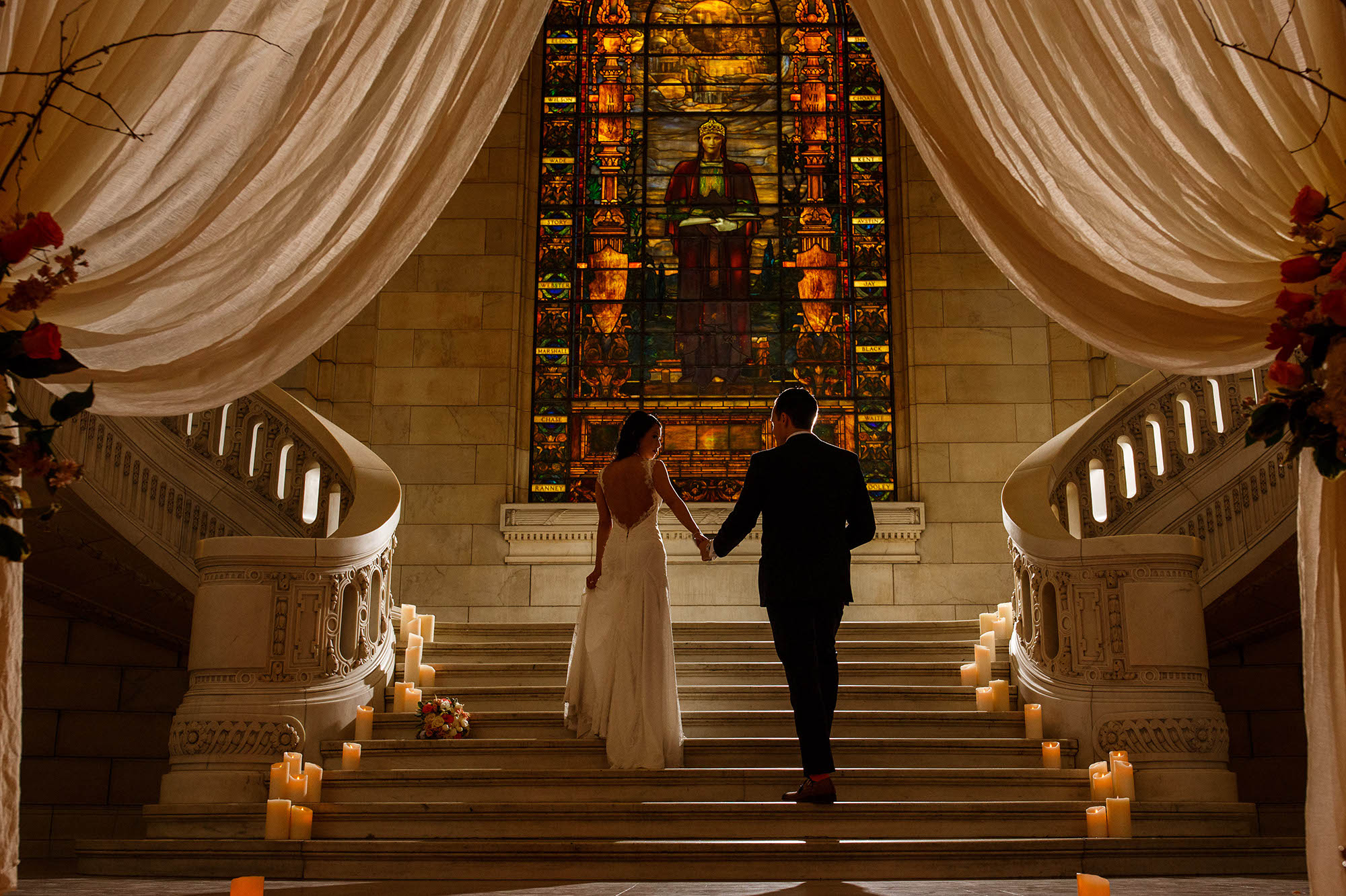 A bride looking over her shoulder at her groom as they are holding hands and walking up a set of ornate steps at the Old Courthouse in downtown Cleveland, Ohio.