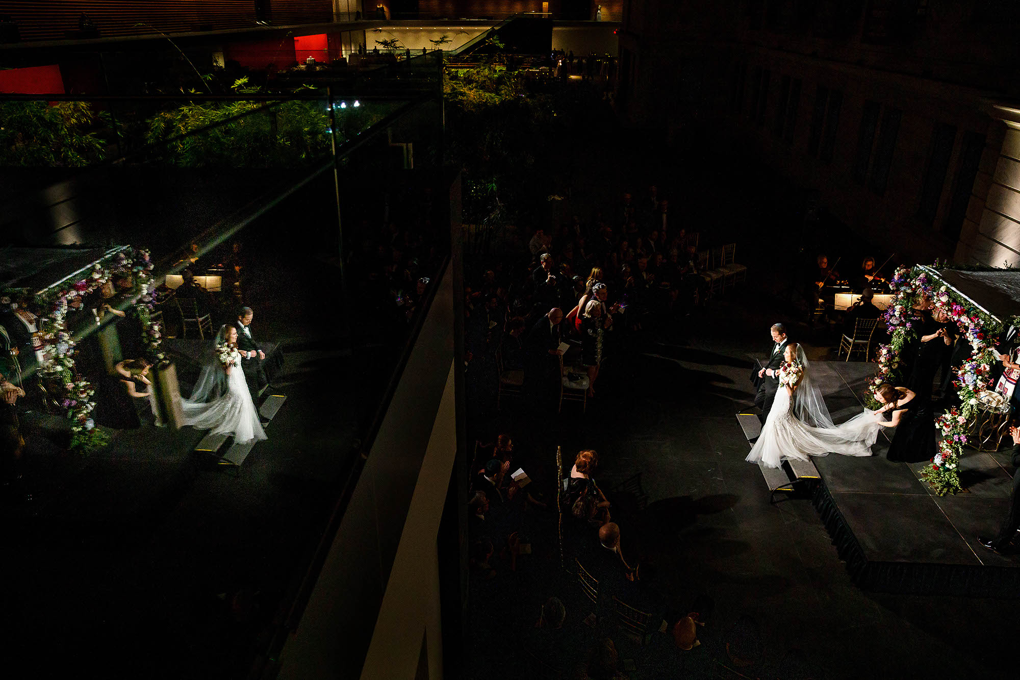 Newly married couple walking back down the aisle at the end of the wedding ceremony inside the Cleveland Museum of Art where their image is being reflected on the widows across from them in downtown Cleveland, Ohio.