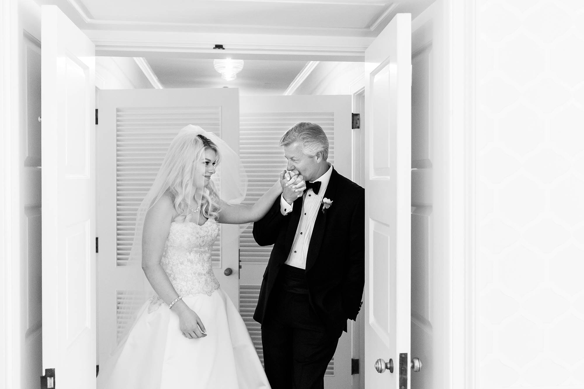 Father of the bride kisses his daughter on the hand moments before she walks down the aisle during their Country Club wedding in Pepper Pike, Ohio.