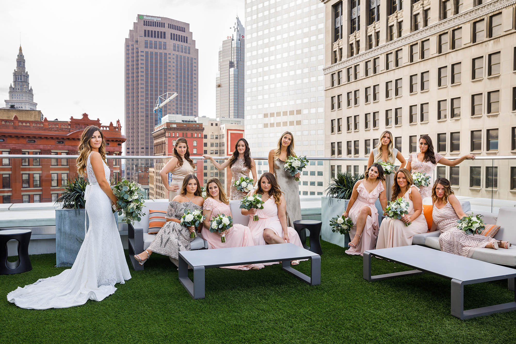 The bride and her bridesmaids on the rooftop bar of The Metropolitan at the 9 with the Cleveland skyline is in the background.