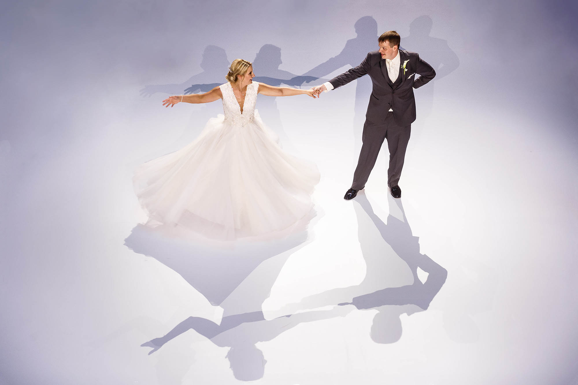 A bride and groom share their first dance on a special white dance floor brought into the Old Courthouse in Downtown Cleveland, Ohio especially for the reception.