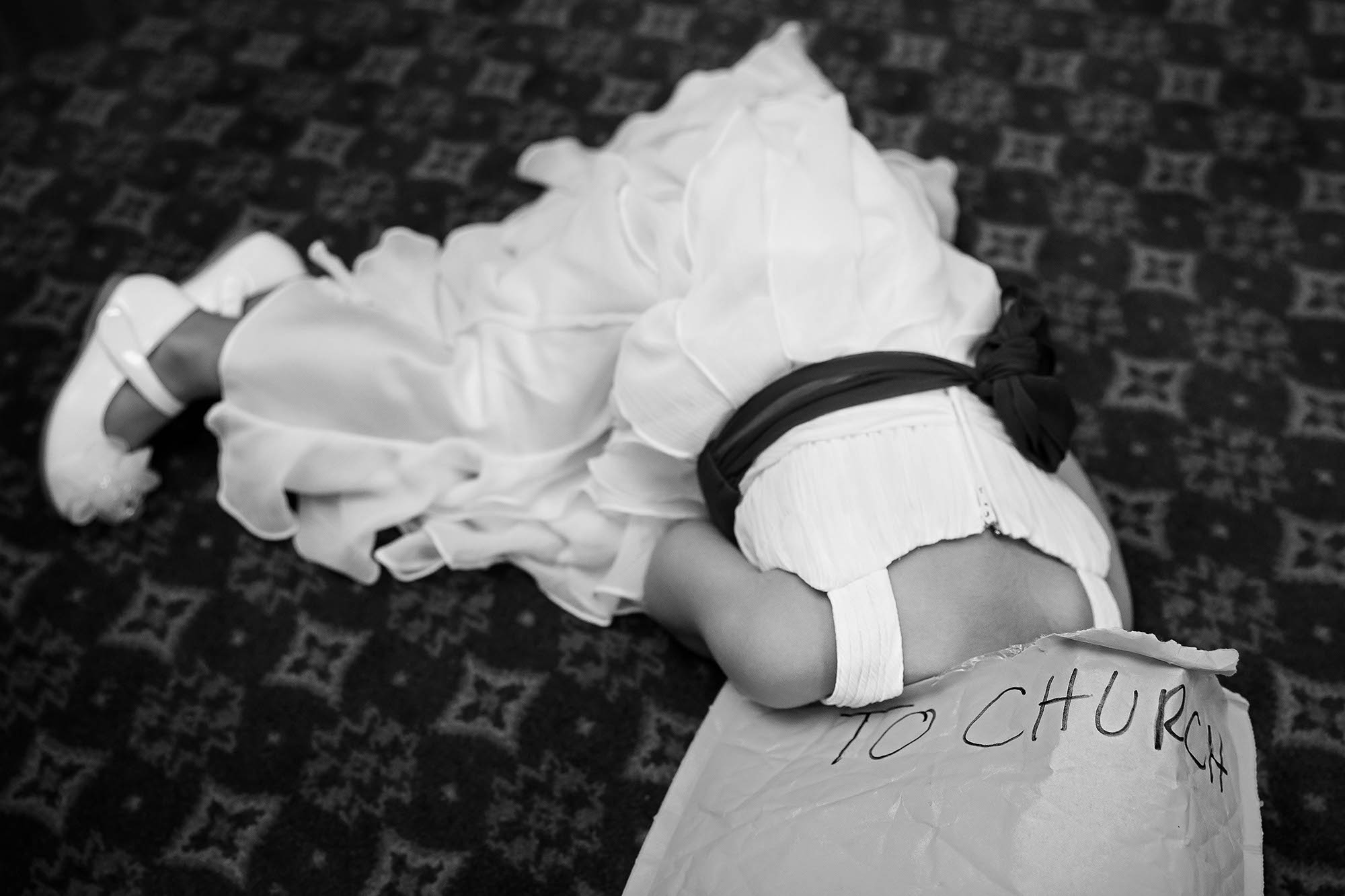 """Flower girl tries to hide inside a manila envelope labeled """"To Church"""" just moments before she is supposed to walk down the aisle."""
