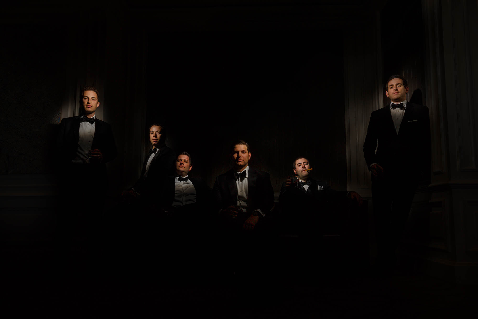 A groom with his groomsmen where each face was was lit up while the rest of the image remained dark.