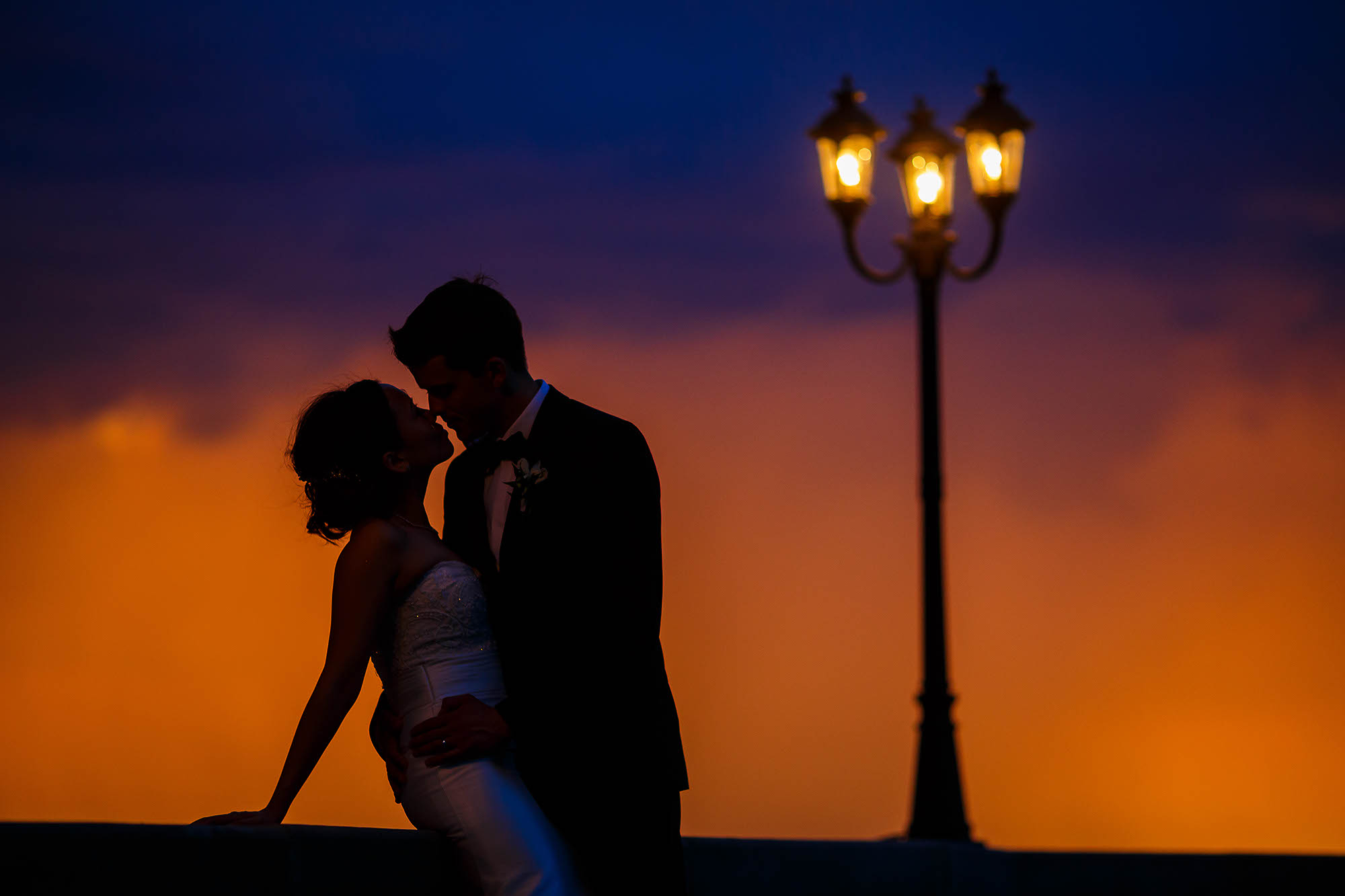 Bride and groom standing in each others arms at sunset outside the Shoreby Club during the wedding reception in Cleveland, Ohio