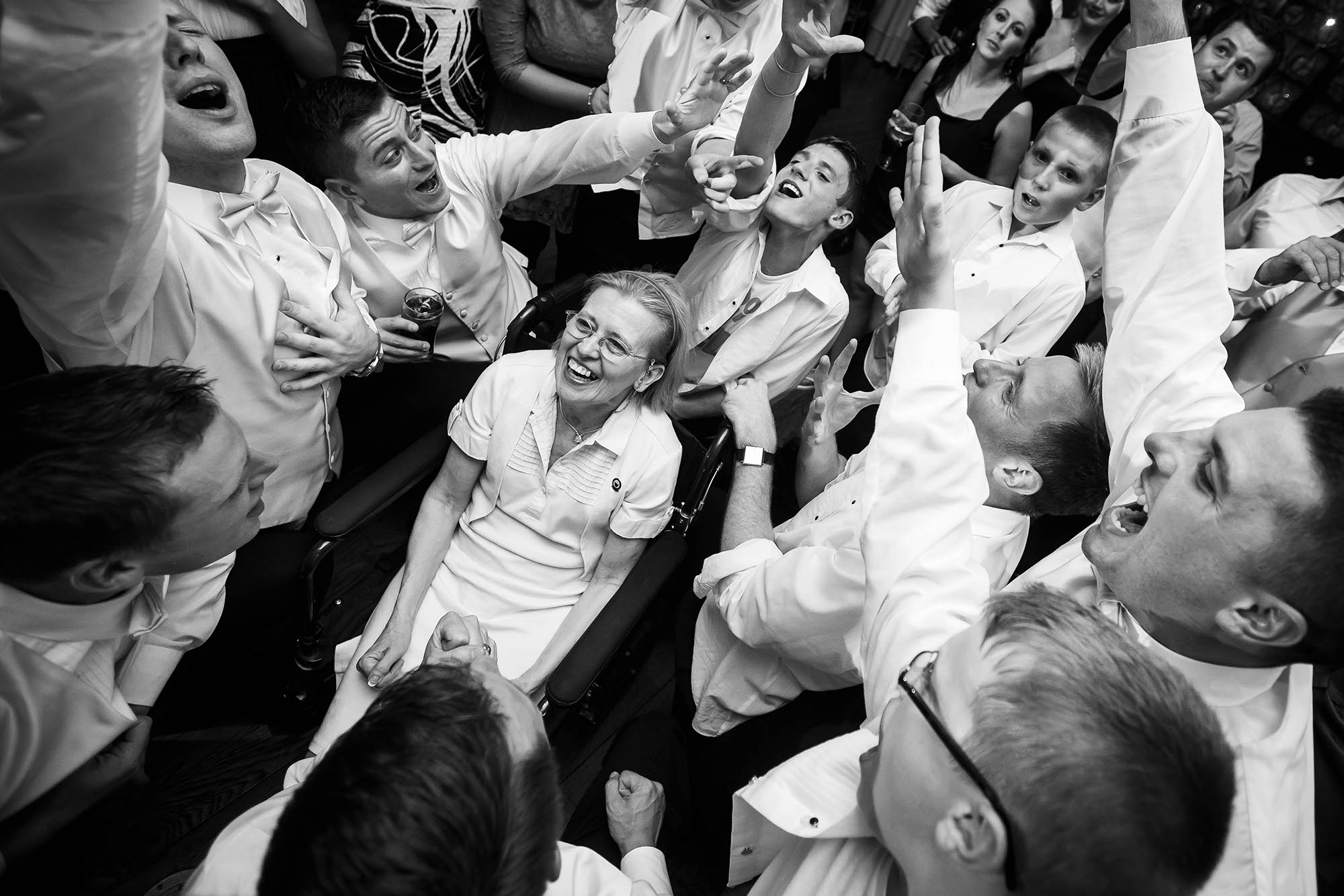 The bride's wheelchair bound aunt beams with joy as the groomsmen serenade her on the dance floor during the reception at Kirkland Country Club.