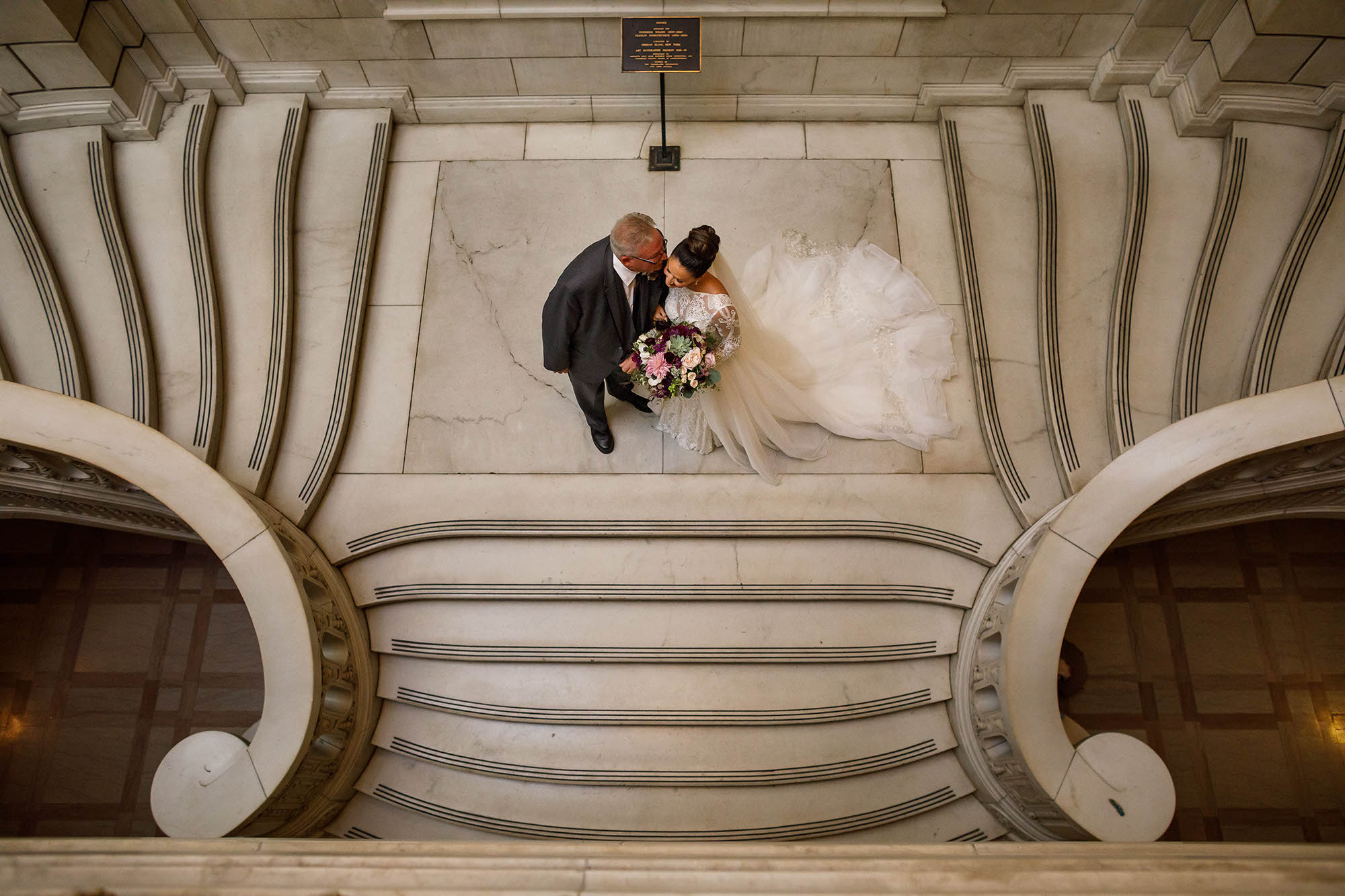 Father of the groom gives his daughter one last kiss on the cheek before walking down the aisle at The Old Courthouse in Downtown Cleveland.