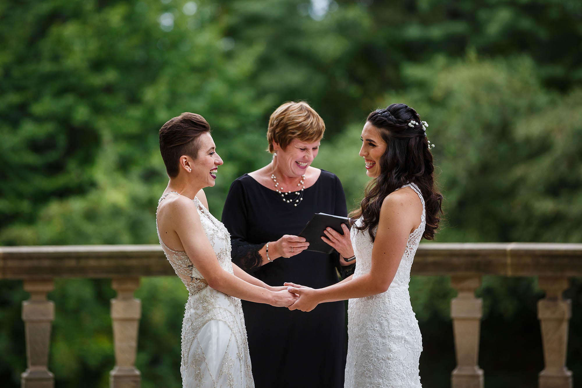 A lighthearted moment between two brides during their outdoor wedding ceremony at Stan Hywet Hall and Gardens in Akron, Ohio on a cement patio overlooking the lush green grounds.