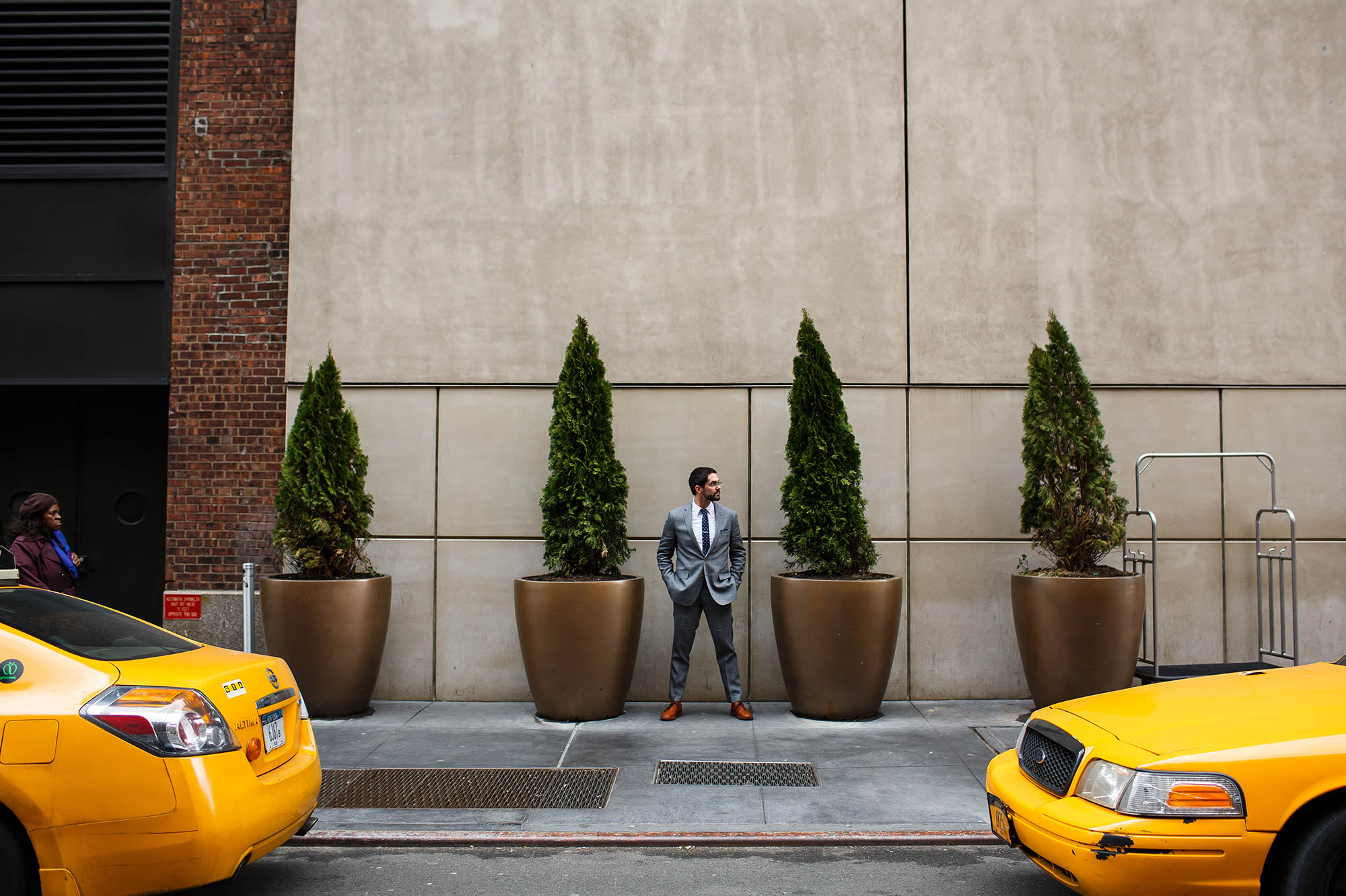 Groom waits for his wedding day to start standing with his hands in his grey suit outside the Hudson Hotel in NYC, New York.
