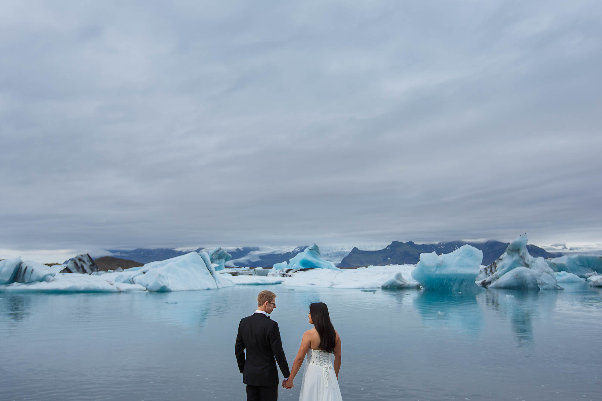 A bride and groom at Jokulsarlon glacier lagoon during their elopement to Iceland.